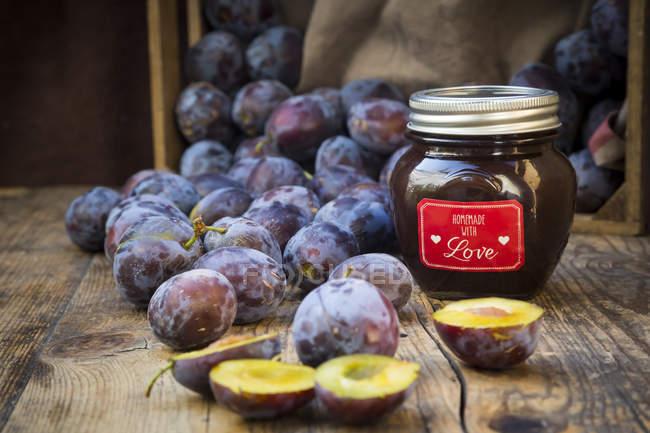Preservando o pote de geleia de ameixa caseiro e ameixas na madeira — Fotografia de Stock