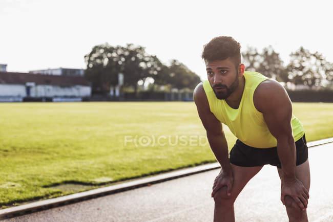 Спортсмен, стоящий на тартановой дорожке — стоковое фото
