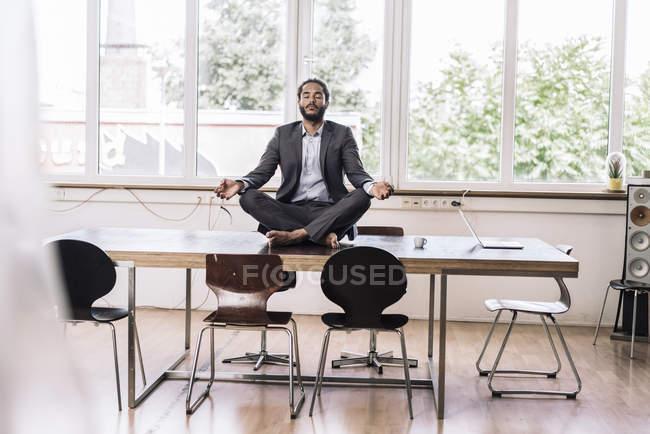 Geschäftsmann sitzt im Schneidersitz auf Schreibtisch — Stockfoto