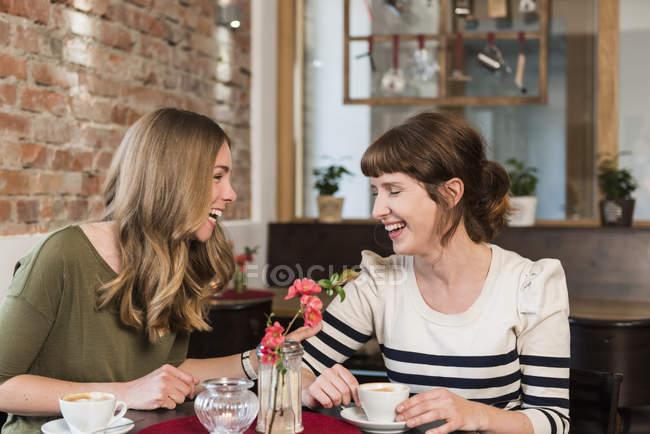 Two best friends sitting in a coffee shop having fun — Stock Photo