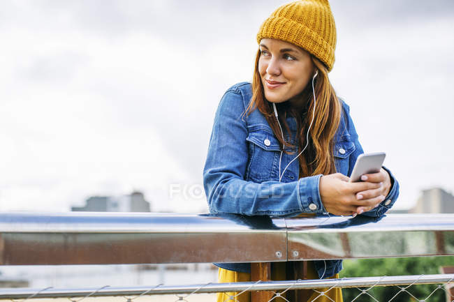 Smiling young woman wearing yellow cap listening music with earphones — Stock Photo
