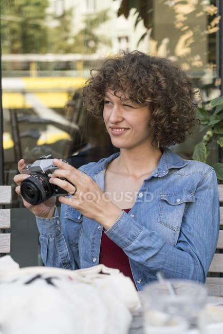 Sorridente giovane donna con vecchia macchina fotografica seduta in un caffè marciapiede — Foto stock