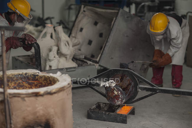 Workers in protective workwear casting metal in a foundry — Stock Photo
