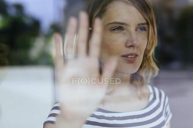 Donna che guarda attraverso la finestra — Foto stock