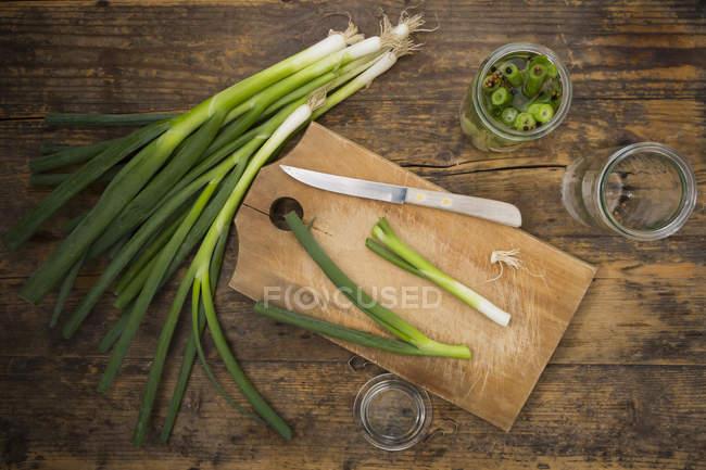 Cebolletas en vinagre en el tablero de madera - foto de stock