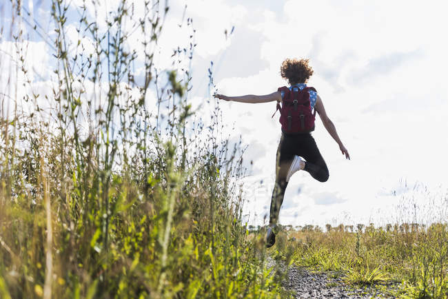 Enthusiastic young woman jumping on field path — Stock Photo