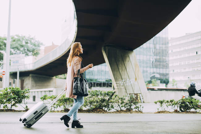 Woman walking with wheeled luggage in city — Stock Photo