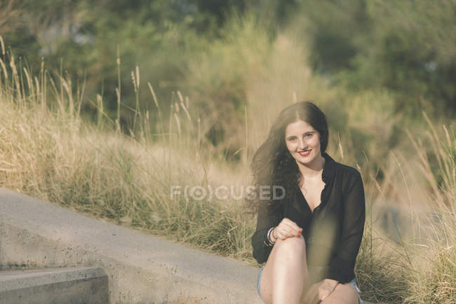 Smiling young woman sitting at wayside — Stock Photo