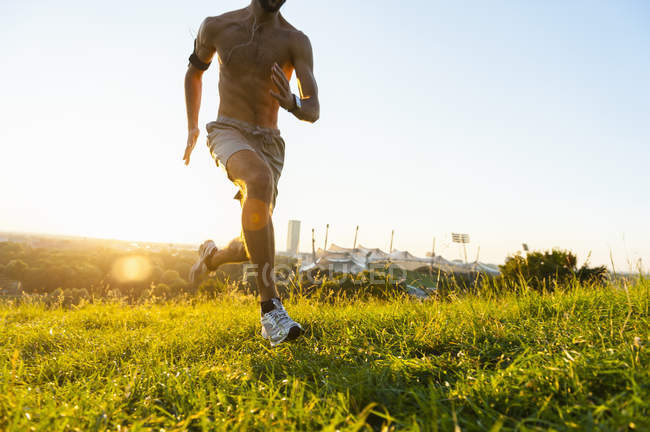 Active man running on meadow in park at sunset — Stock Photo
