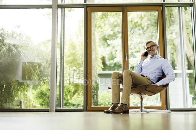 Человек на телефоне сидит на стуле в своей гостиной — стоковое фото