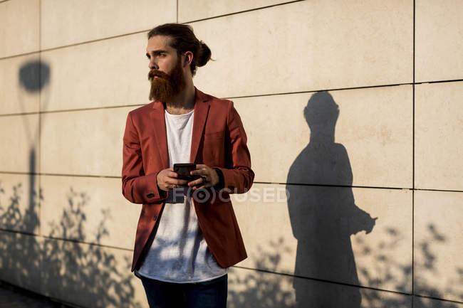Hombre con smartphone mirando a distancia - foto de stock