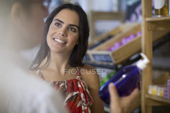 Женщина смотрит на мужчину, держащего автомат с мылом в магазине — стоковое фото