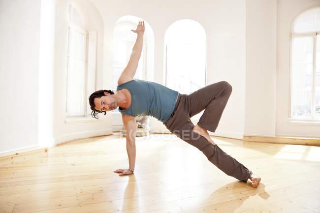 Man in sunny yoga studio holding Vasisthasana pose — Stock Photo
