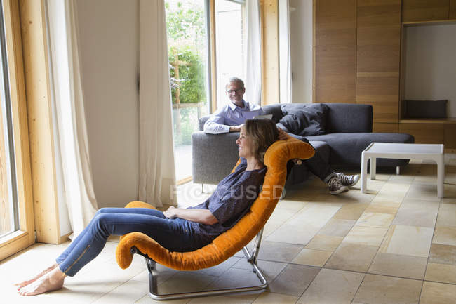 Smiling woman relaxing in armchair with husband in background — Stock Photo