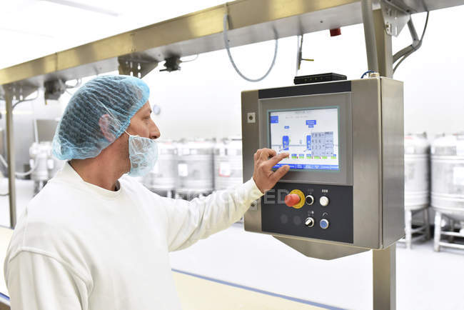 Worker operating machine in an industrial bakery — Stock Photo