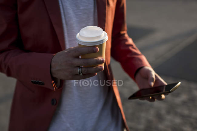 Male hands holding coffee to go — Stock Photo