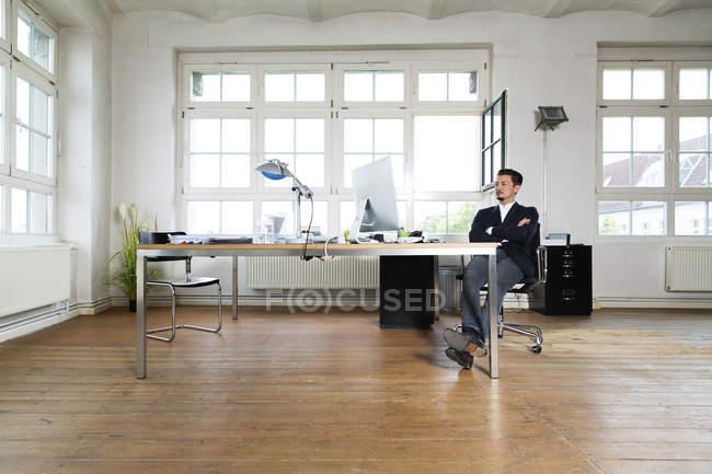 Бизнесмен, сидящий у власти со скрещенным оружием — стоковое фото