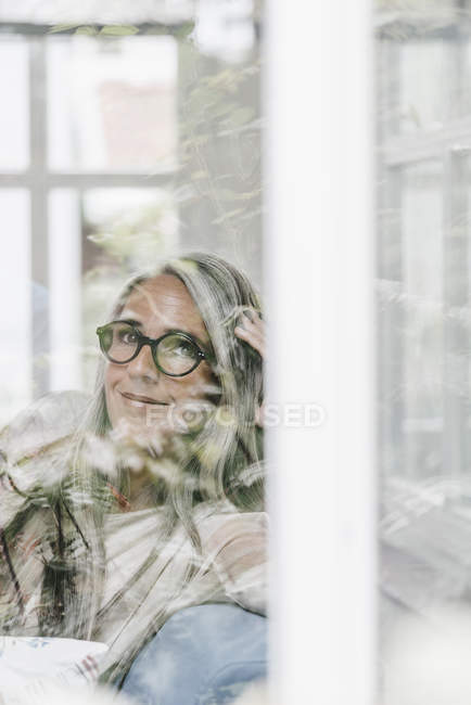 Smiling woman sitting in winter garden — Stock Photo