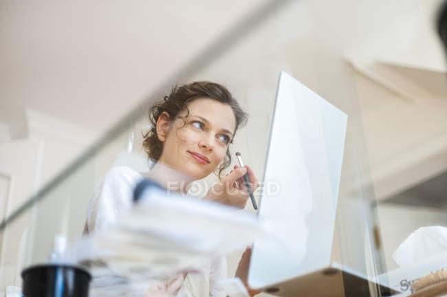 Woman applying eye makeup at home — Stock Photo