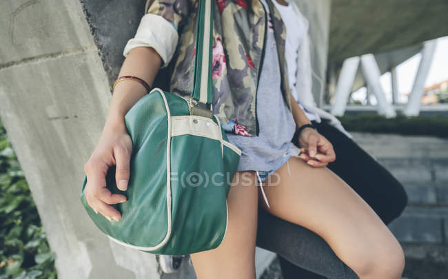 Woman holding green shoulder bag, partial view — Stock Photo