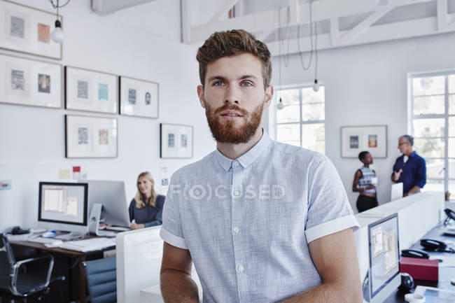 Businessman in office with staff in background — Stock Photo