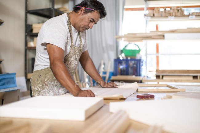 Man looking at plans in canvas workshop — Stock Photo