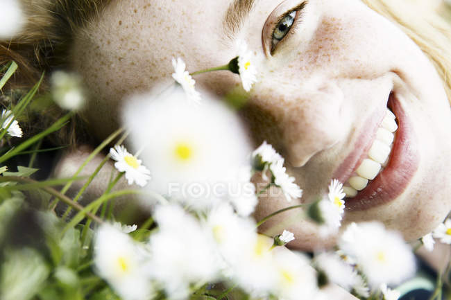Smiling girl lying on the field of flower — стоковое фото
