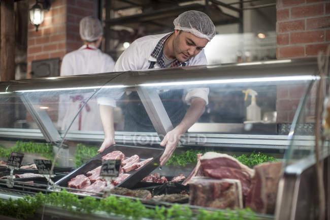 Boucher exposant de la viande fraîche en boucherie — Photo de stock