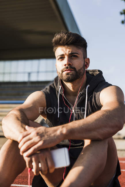 Young man with earbuds sitting on tartan track — Stock Photo