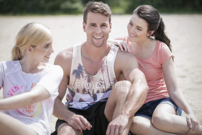 Tres amigos sentados en la playa y divirtiéndose - foto de stock