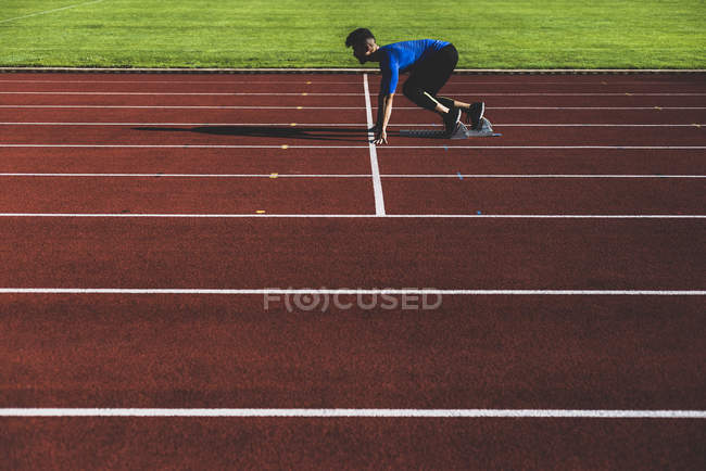 Runner on tartan track in starting position — Stock Photo