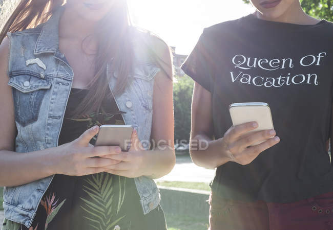 Two female friends with smartphones — Stock Photo
