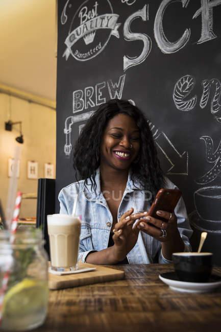 Женщина в кафе, с помощью смарт-телефон — стоковое фото