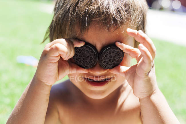 Little boy covering his eyes with chocolate cookies — Stock Photo