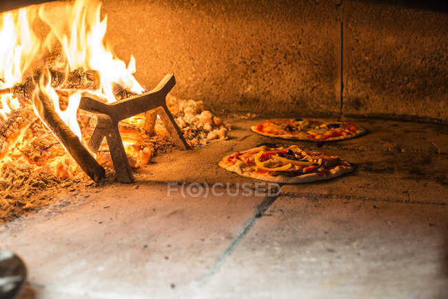 Pizzas in traditional oven — Stock Photo