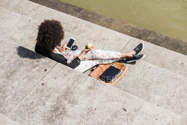 Жінка харчової apple і за допомогою смартфона — стокове фото