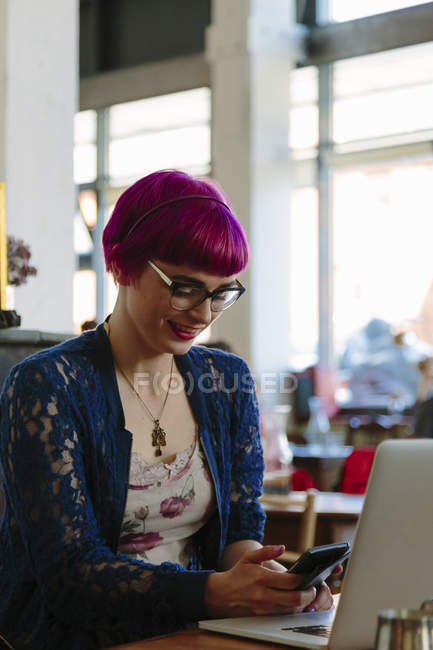 Smiling young woman with dyed hair sitting in a coffee shop text messaging — Stock Photo