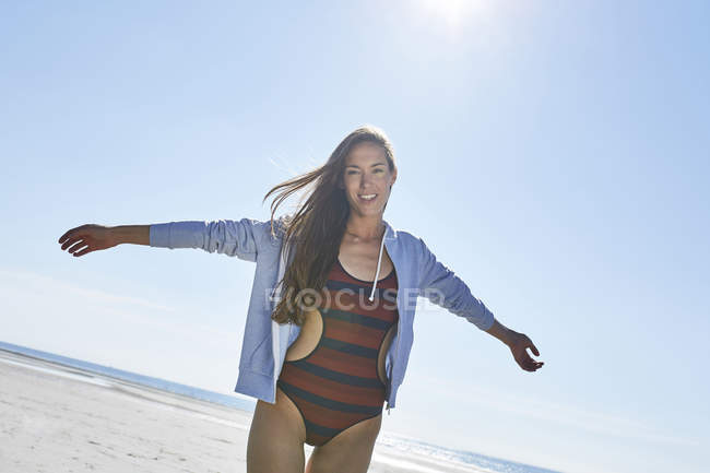 Glückliche junge Frau mit ausgestreckten Armen am Strand — Stockfoto