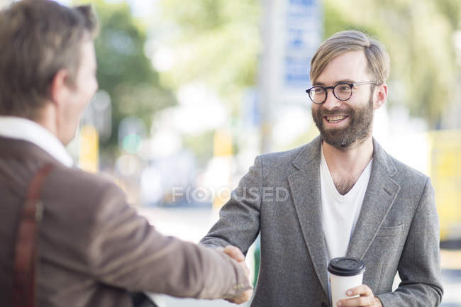 Two men shaking hands outdoors — Stock Photo