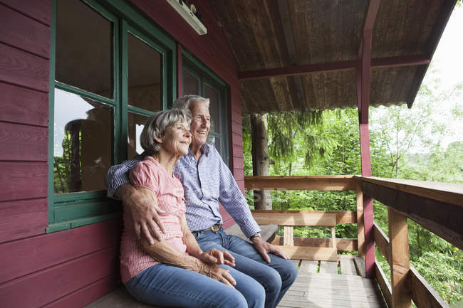 Happy senior couple relaxing on porch of log cabin — Stock Photo