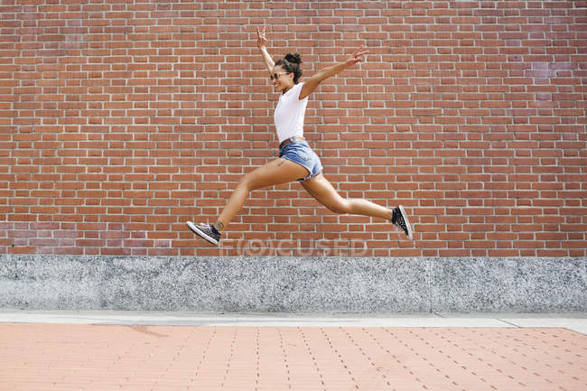 Exuberant young woman jumping  in front of a brick wall — Stock Photo