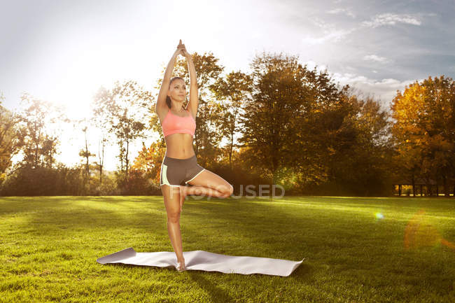 Woman standing in tree position in park — Stock Photo