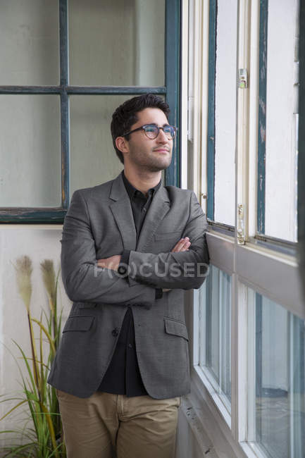 Businessman standing at the window with arms crossed — Stock Photo