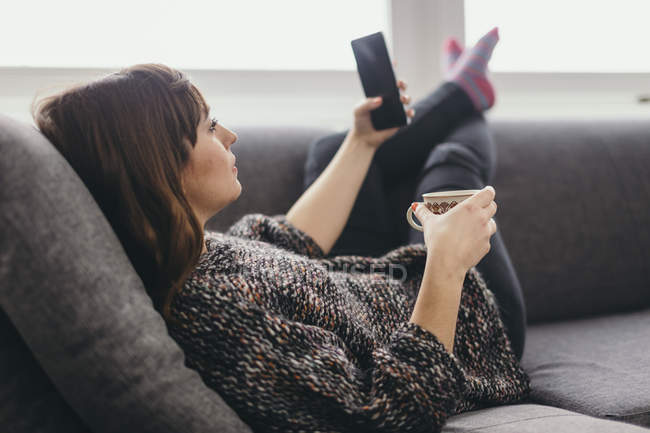 Giovane donna rilassante sul divano con tazza di caffè scattare selfie con smartphone — Foto stock