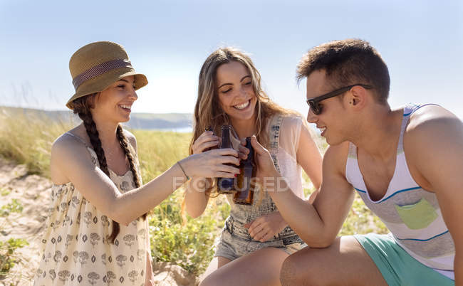 Three friends toasting with beer bottles on the beach — Stock Photo