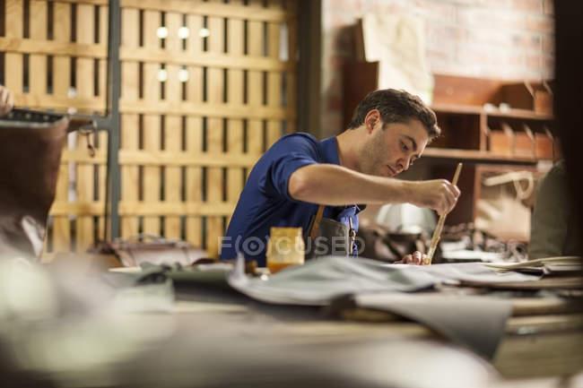 Человек, работающий в кожевенной мастерской — стоковое фото