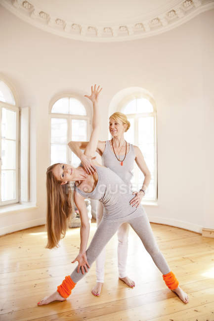 Woman in sunny yoga studio holding extended triangle pose with the help of her instructor — Stock Photo