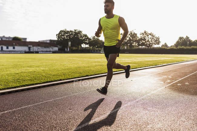 Athlete running on tartan track — Stock Photo