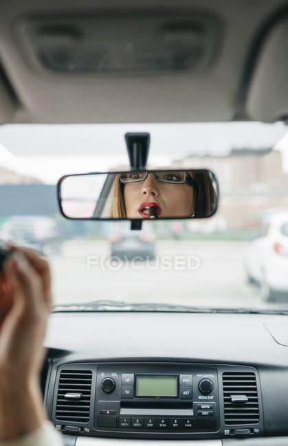 Woman in car applying lipstick — Stock Photo