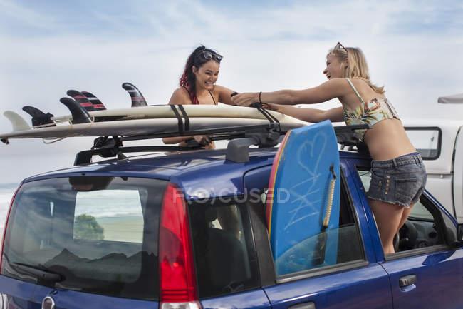 Молоді жінки, розгортаючи дошки для серфінгу на автомобіль — стокове фото